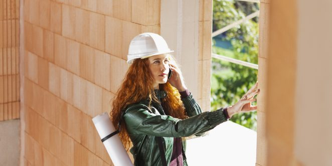 Female architect with hard hat and blueprint-casing inside a building shell touching a brick
