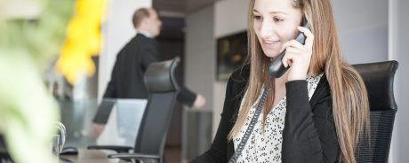 Young woman at reception desk on the phone