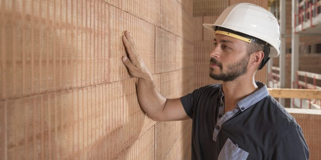 Man with safety helmet touching bare brick wall