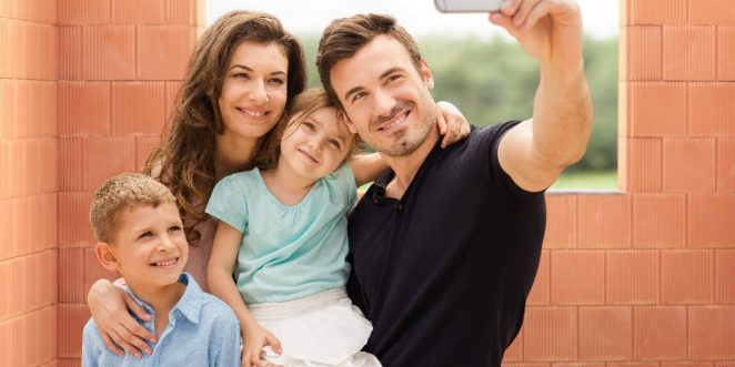 Parents with two kids taking a selfie with mobile phone inside new built house in front of bare clay block walls